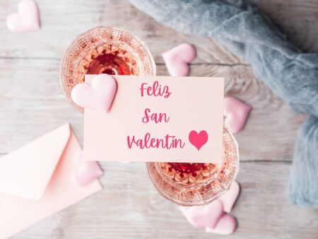 Happy valentines day greetings in Spanish. Greeting card with text. Two stemmed champagne glasses with pink hearts on wooden textured background.