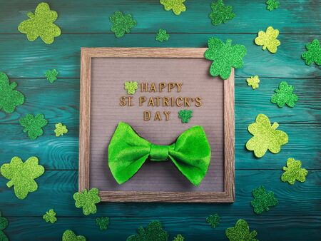 St Patrick Day greetings on letter board on dark green wooden rustic background with shamrocks and leprechaun costume accessories