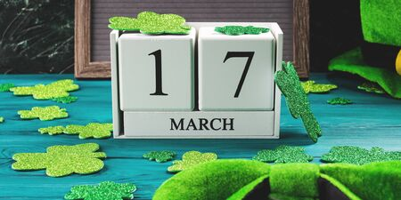 St Patricks Day date 17 march on wooden calendar on dark green wooden rustic background with shamrocks and leprechaun costume accessories