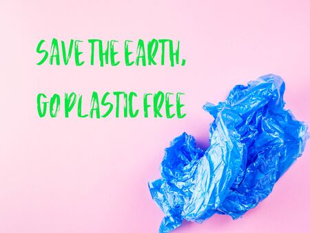 Crumpled blue plastic trash bag on pink background. Recycling, going plastic free concept. Save the Earth, Go plastic free text