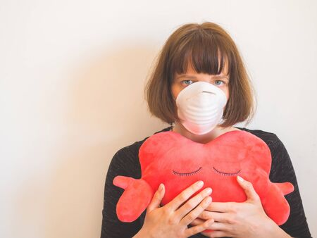 Frustrated caucasian young woman wearing face mask and hugging heart shaped plush toy as symbol of support and hope staying home during Coronavirus pandemic quarantine Stock Photo