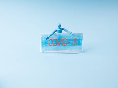 Coronavirus pandemic concept with wooden marionette holding medical face mask with text message Covid-19 on blue background