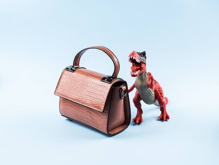 Angry dinosaur toy and lady hand bag. Fashion concept. Sale Stockfoto - 145339066