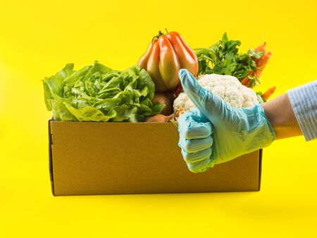 Fresh produce, food staples delivery or donation box concept on yellow background. Hand in blue medical glove with thumb up. Safe shopping and delivery during coronavirus pandemic