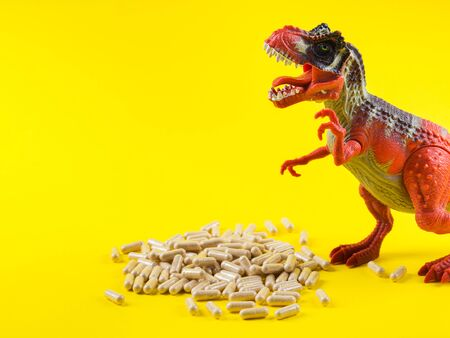 Maca powder in capsules on yellow background with funny toy dinosaur above the pills. Food supplement for energy boosting.