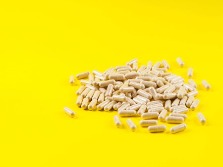 Maca powder in capsules on monochrome yellow background. Food supplement for energy boosting. Stock Photo