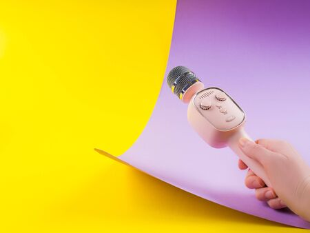 Pastel pink wireless karaoke microphone in female hand with copy space on modern yellow and purple background. Interview, performance concept