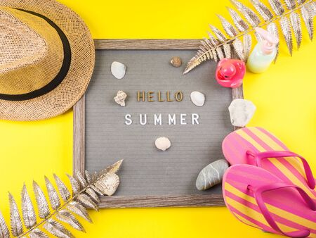 Hello summer text on letter board on yellow background with straw hat, flip flops, seashells and stones, golden tropical branches. Flat lay