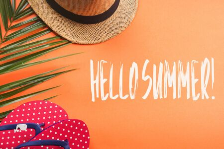 Vacation on the beach. Flat lay on orange coral background. Fern, hat, flip flops. Hello summer text Banque d'images