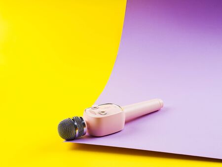 Pastel pink wireless karaoke microphone on colorful yellow and purple background. Singing, performance concept