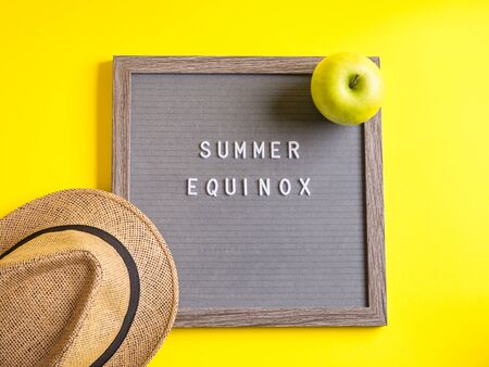 Summer equinox text on letter board on yellow background with straw hat and apple as sun symbol. Hello summer concept Banque d'images
