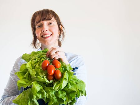 Delivery girl or small shop owner wearing blue apron holding fresh produce - fresh vegetables, pasta and milk - in gloved hands. Food delivery, local grocery shopping