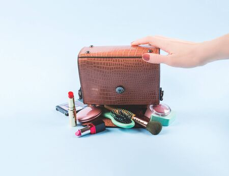 Reptile print lady hand bag upside down with make up items held by female hand. Fashion beauty concept. Sale