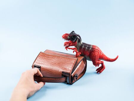 Angry dinosaur toy and lady hand bag held by female hand. Funny fashion concept. Sale