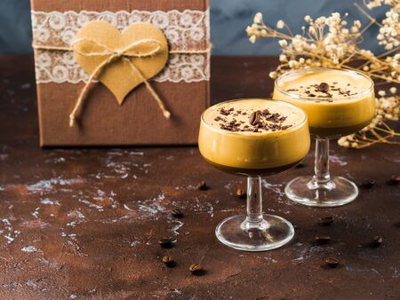 Frappe frothed cold coffee drink in dessert stemmed glasses on brown wooden board with gift box with heart. Valentines day, mothers day Banque d'images