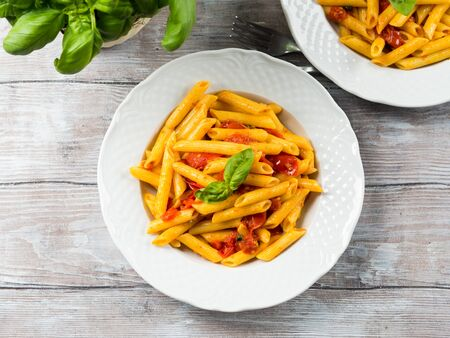 Penne pasta with fresh tomatoes and basil on wooden table. Traditional italian dish Фото со стока