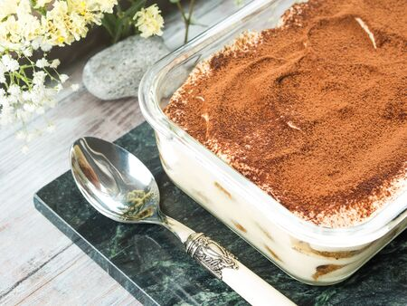 Traditional coffee tiramisu dessert with mascarpone cheese and cocoa powder in glass container on green marble board