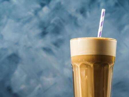 Frappe milk shake coffee in tall glass on blue and brown background. Straw