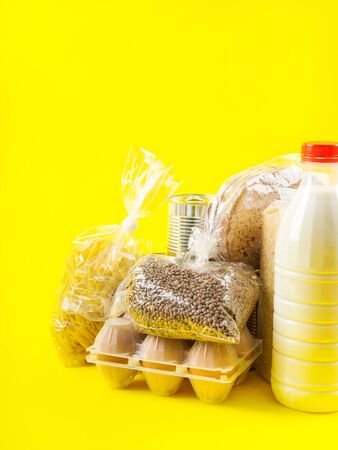 Food staples delivery or donation box concept on yellow background. Closeup