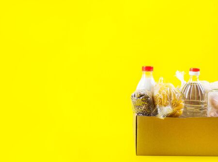 Food staples delivery or donation box concept on yellow background Archivio Fotografico - 149594881