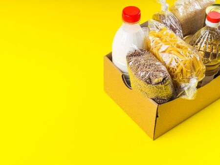 Food staples delivery or donation box concept on yellow background