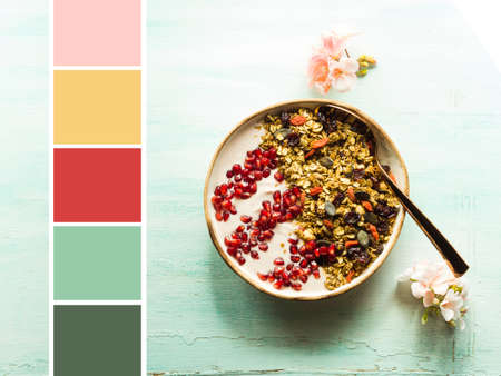 Home made smoothie bowl with yogurt and pomegranate with granola of dried fruit, seeds and nuts. Color swatch