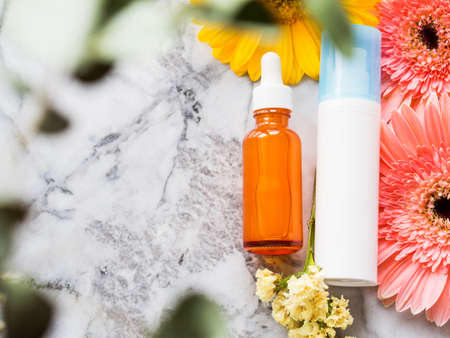 Face cream in white pump dispenser and anti aging serum in glass bottle on marble board with beautiful yellow and pink flowers. Skin care concept with eucaliptus blurred frame