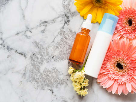 Face cream in white pump dispenser and Vitamin C serum in glass bottle on marble board with beautiful yellow and pink flowers. Skin care concept, copy space Stock Photo