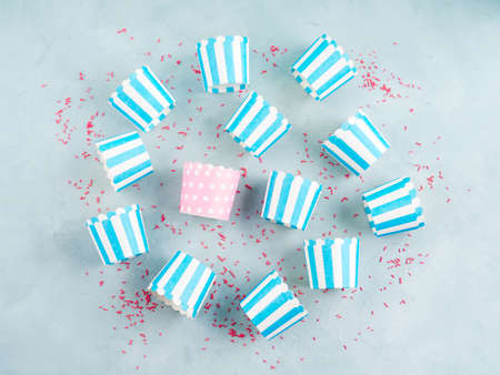 Pastel blue striped paper cases for baking cup cakes with one different pink on gray background. Sweet pastry concept, flat lay.