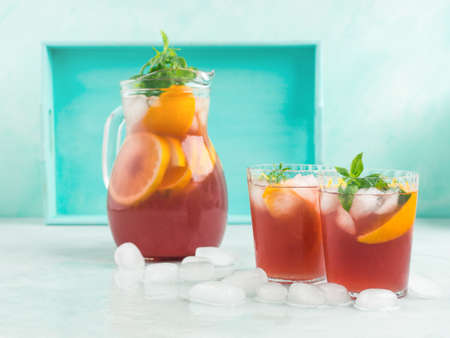 Fresh red cocktail mocktail sangria in pitcher and glasses with ice, mint leaves and lemon and orange slices on bright turquoise background