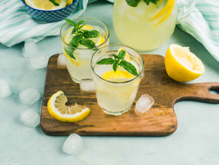 Fresh lemonade in jug and glasses with ice, mint leaves and lemon slices on bright gray and blue background. Top view