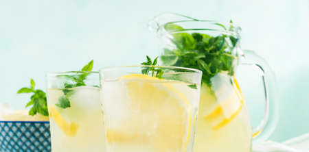 Fresh lemonade in jug and glasses with ice, mint leaves and lemon slices on bright gray and blue background. Closeup banner