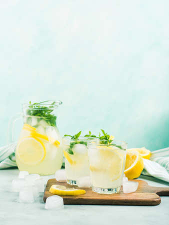 Fresh lemonade in jug and glasses with ice, mint leaves and lemon slices on bright gray and blue background