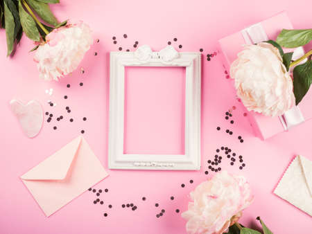 Pink pastel delicate greeting card background with floral decor with peonies and gift boxes. Flat lay mockup with confetti frame, envelopes