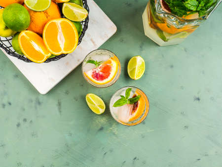 Fresh summer citrus lemonade with lime, mint, blood oranges and ice cubes in jar and glasses over green textured background. Flat lay