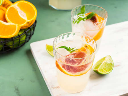 Fresh summer citrus lemonade with lime, mint, blood oranges and ice cubes in jar and glasses over green textured background. Banco de Imagens