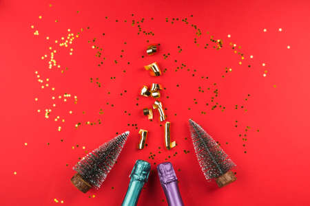 Champagne bottle with golden streamers, confetti and toy xmas trees on red color background. Celebrating new year, christmas, valentine's day festive flat lay.