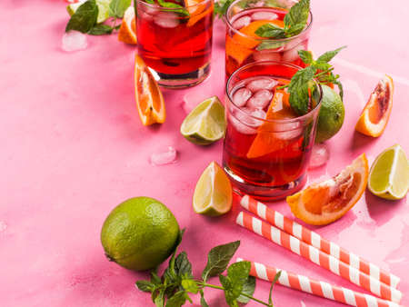 Fresh iced red cocktail in pink glasses with blood orange and lime on pink background garnished with mint leaves. Closeup