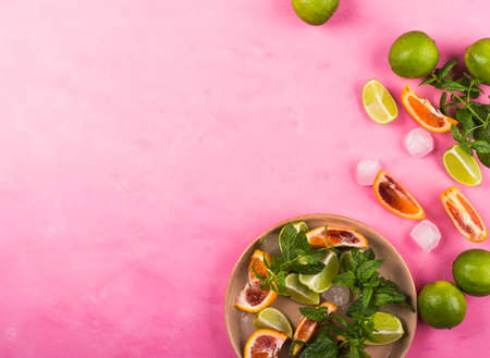 Lime and blood orange slices, ice, mint leaves over pink background. Ingredients for fresh summer iced cocktail, flat lay