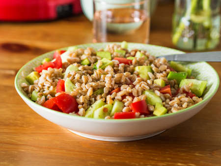 Fresh Italian farro spelt salad with tomatoes, avocado and cucumbers on wooden kitchen table. Easy recipe whole food meal