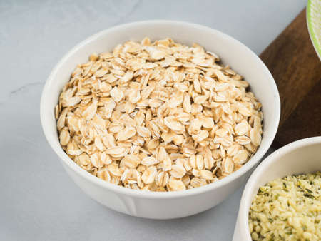 Oat flakes in bowl on gray background. Closeup