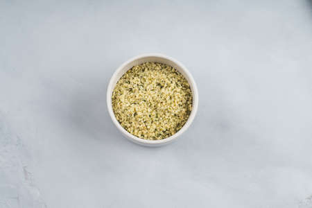 Shelled hemp seeds superfood in white bowl over gray background. Top view