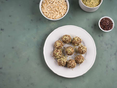 Home made vegan energy protein balls with oats, nuts, dates, dried fruit, flax and hemp seeds, chocolate nibs and maple syrup on white dish over green textured background. Flat lay