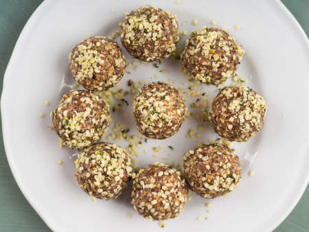 Home made vegan energy protein balls with oats, nuts, dates, dried fruit, flax and hemp seeds, chocolate nibs and maple syrup on white dish over green textured background. Closeup