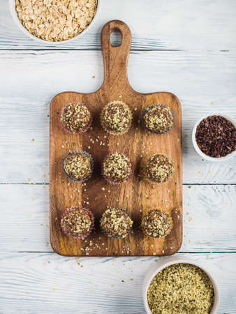 Home made vegan energy protein balls with oats, nuts, dates, dried fruit, flax and hemp seeds, chocolate nibs and maple syrup served in paper cases on wooden board. Flat lay, vertical