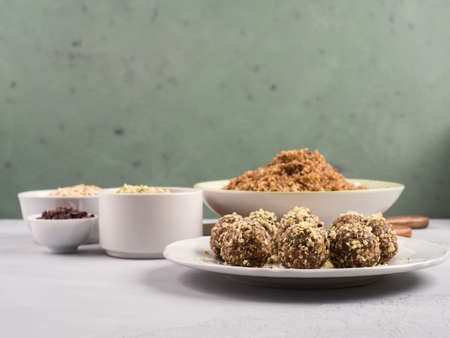Home made vegan energy protein balls with oats, nuts, dates, dried fruit, flax and hemp seeds, chocolate nibs and maple syrup on white dish over gray and green stone background. Banco de Imagens