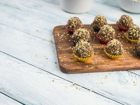 Home made vegan energy protein balls with oats, nuts, dates, dried fruit, flax and hemp seeds, chocolate nibs and maple syrup served in paper cases on wooden board. Copy space