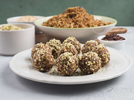 Home made vegan energy protein balls with oats, nuts, dates, dried fruit, flax and hemp seeds, chocolate nibs and maple syrup on white dish over gray and green stone background. 스톡 콘텐츠