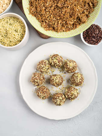 Home made vegan energy protein balls with oats, nuts, dates, dried fruit, flax and hemp seeds, chocolate nibs and maple syrup on white dish over gray stone background. Flat lay