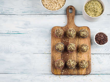 Home made vegan energy protein balls with oats, nuts, dates, dried fruit, flax and hemp seeds, chocolate nibs and maple syrup served in paper cases on wooden board. Flat lay